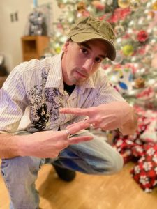 Ziggy, wearing a short sleeve white polo shirt with light blue jeans, crouches in front of a Christmas tree with his hands towards the camera making a Z with his fingers. He's a white man wearing an olive green baseball hat.