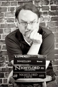 Black and White photo of Garon Whited who leans on a stool. His chin rests on his right hand, and a stack of his books is on the stool.