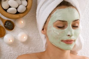 A white woman with a green clay mask and white towel wrapped around her head lays in front of a few tea light candles and basket of rocks. She's at a spa.