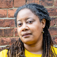 Headshot of NK Jemisin: a black woman with dark brown box braids pulled back in a ponytail stands in front of a brick wall wearing a yellow shirt.