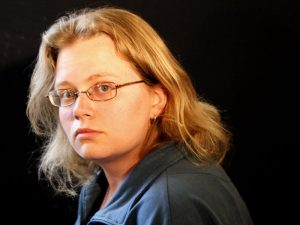 Headshot of Seanan, a white woman with mid-length blond hair, wearing glasses and a blue collared blouse